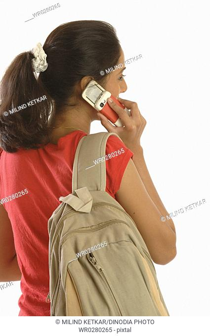College going young girl with sack type of bag talking on mobile phone MR748O