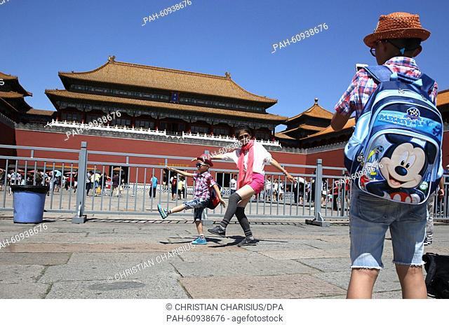 Chinese tourists take pictures at the entrance to a palace of the Forbidden City on Tian'anmen Square in Beijing, China, 21 August, 2015