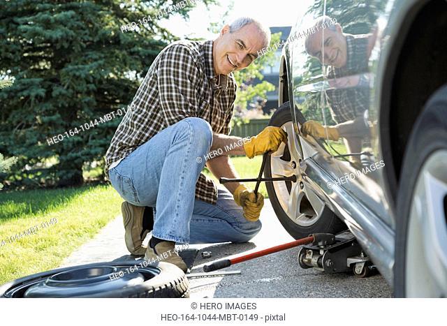 Portrait of mature man changing car tire