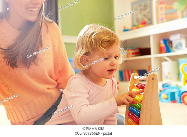 Mid adult woman and toddler daughter counting on abacus in playroom