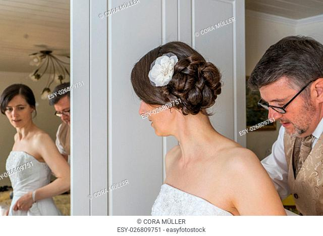 The groom helps the bride to dress