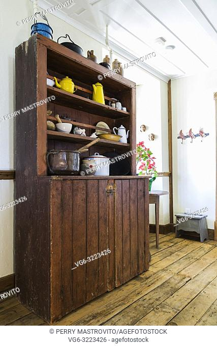Old antique wooden buffet with pots and crockery in a hallway on the ground floor inside an old 1835 fieldstone house