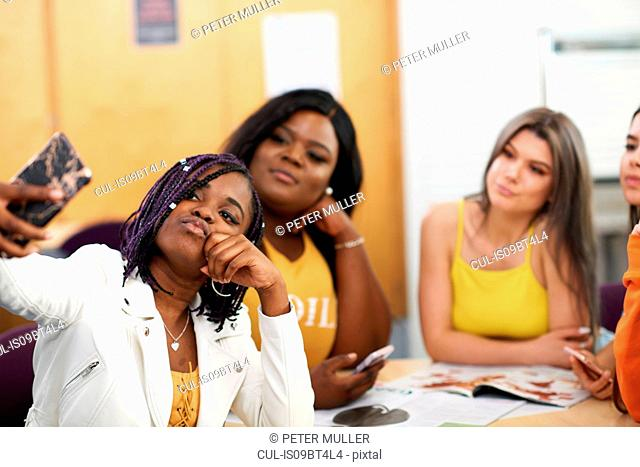 Female higher education students taking selfie in college classroom