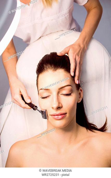 Dermatologist performing laser hair removal on patient