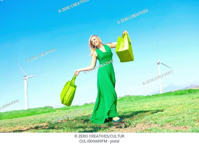 Woman in field with green shopping bags