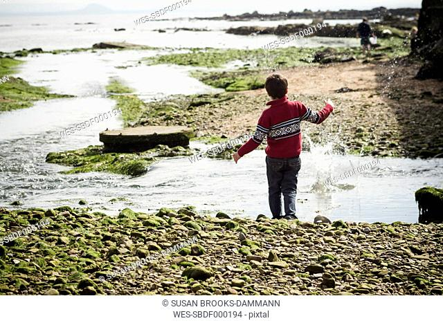 Great Britain, Scotland, Fife, Anstuther, boy at the beach throwing stones into water