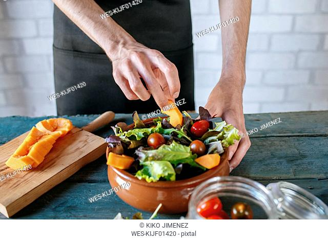 Man preparing batavia lettuce salad, partial view