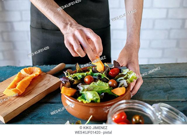 Man preparing batavia lettuce salad, partial view