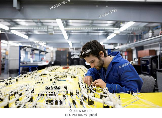 Helicopter technician repairing wiring harness