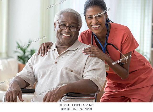 Caregiver smiling with older man in wheelchair