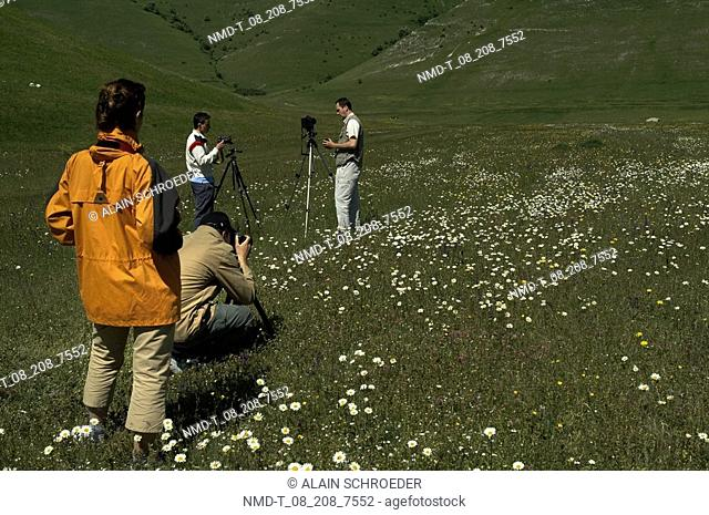 Mid adult men with a mid adult woman photographing in a field