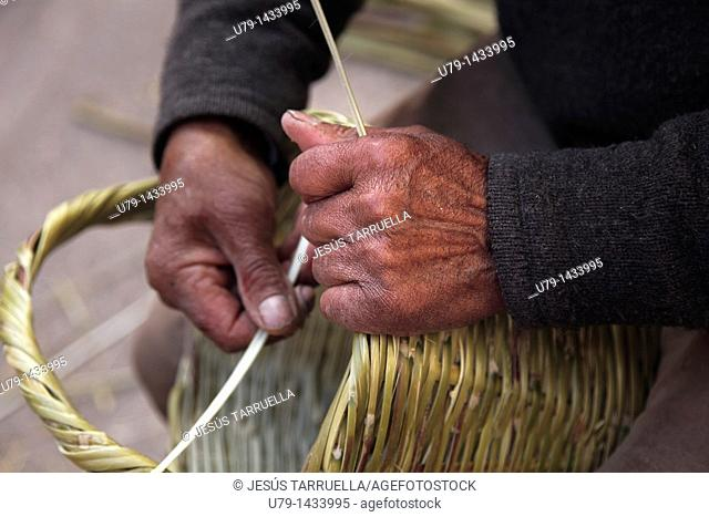 Detail of the hands of a craftsman working on a basket in Villena Medieval Fair on March 15, 2011