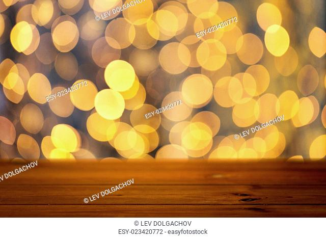 holidays, new year and celebration concept - close up of empty wooden surface or table over christmas golden lights background