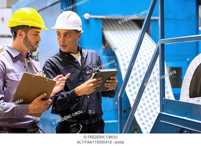 Factory workers discussing with each other in factory