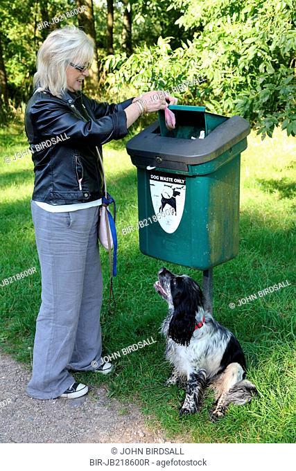Woman putting dog mess into bin
