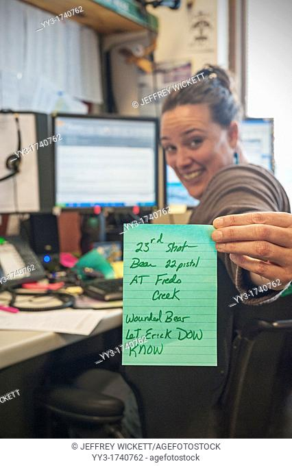 US Forest Service dispatcher holds up message for field workers - warning of wounded bear in their work area on the Tongass National Forest, Alaska, USA