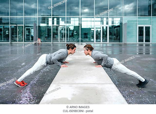 Young male twins doing push ups against wall in city, full length