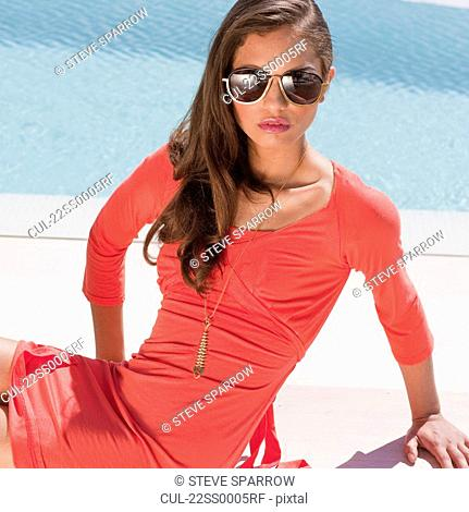 Beautiful young woman sitting by pool