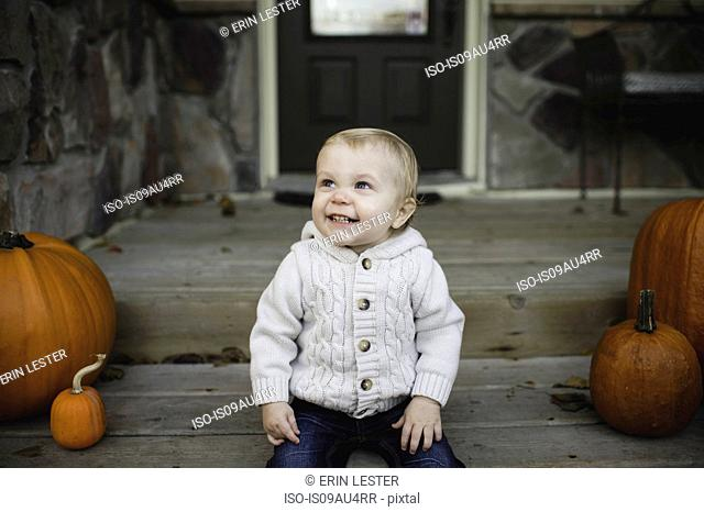 Baby boy sitting on front porch with pumpkins looking up smiling