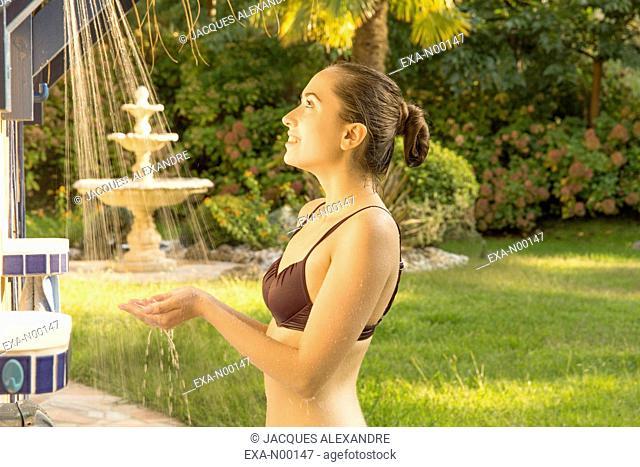 Woman in swimsuit in outdoor shower