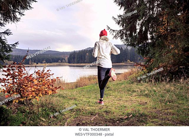 Germany, Thuringia, woman running through the forest by the lake near Alsbach