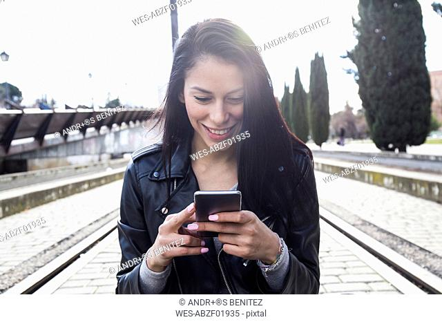 Portrait of smiling young woman wearing black leather jacket looking at cell phone