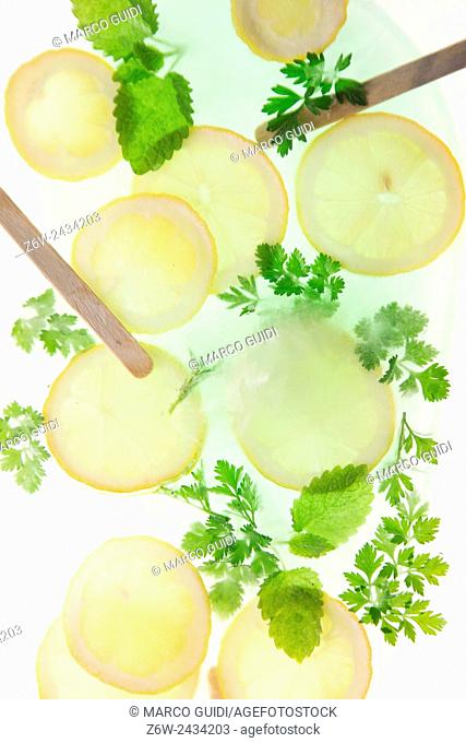 Slices of lemon with mint leaves and sprigs of parsley