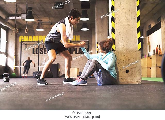 Athlete helping young woman getting up after a break in gym