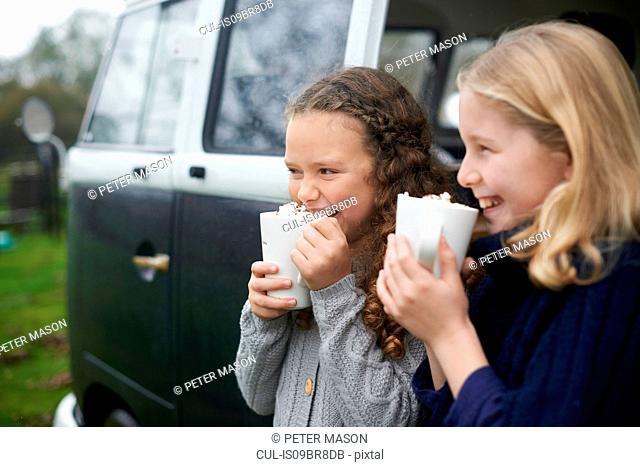 Girls drinking hot chocolate beside camper van