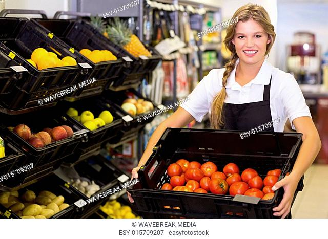 Portrait of a staff woman holding a box with a fresh vegetables
