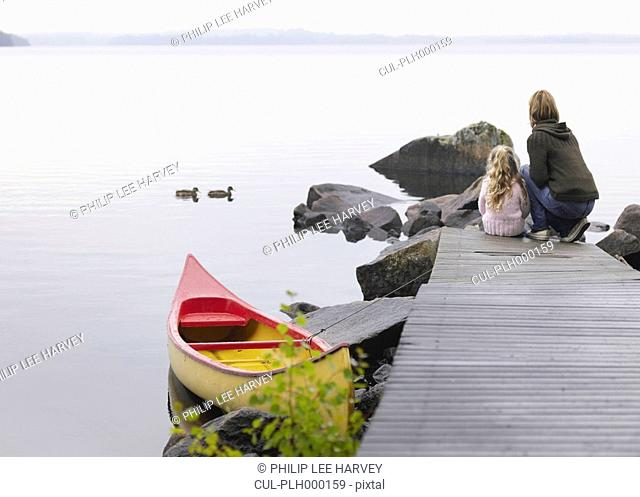 Woman and young girl on a dock near a boat