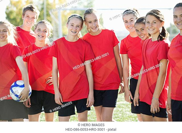 Girls soccer team smiling in red jerseys