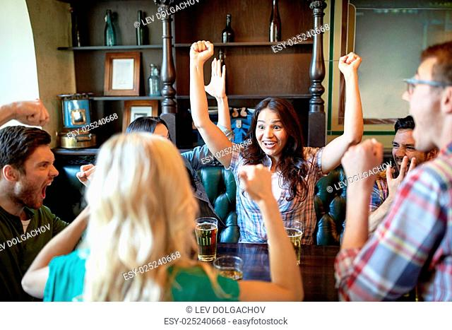 people, leisure, friendship and celebration concept - happy friends with beer celebrating victory at bar or pub