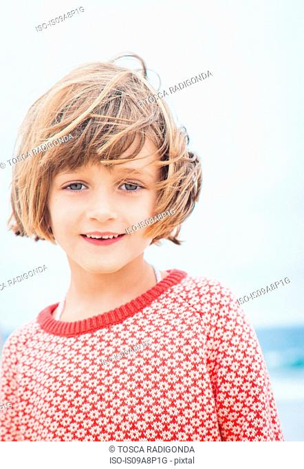 Child with wind blown hair looking at camera