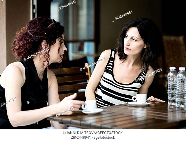 Two women chatting at a coffee shop