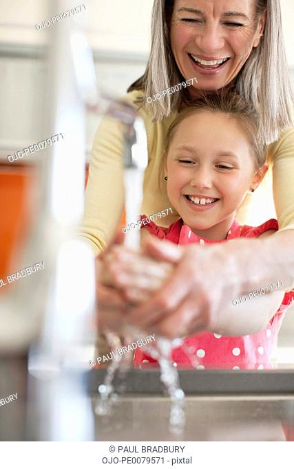 Grandmother helping granddaughter to wash her hands