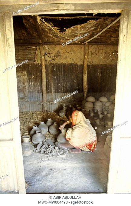 A woman works on earthen pots and vases Colourful earthenware like pots, jars, and vases enhance the beauty of city households Besides