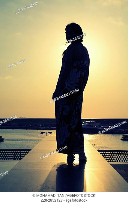 Full length silhouette of a woman at sunset