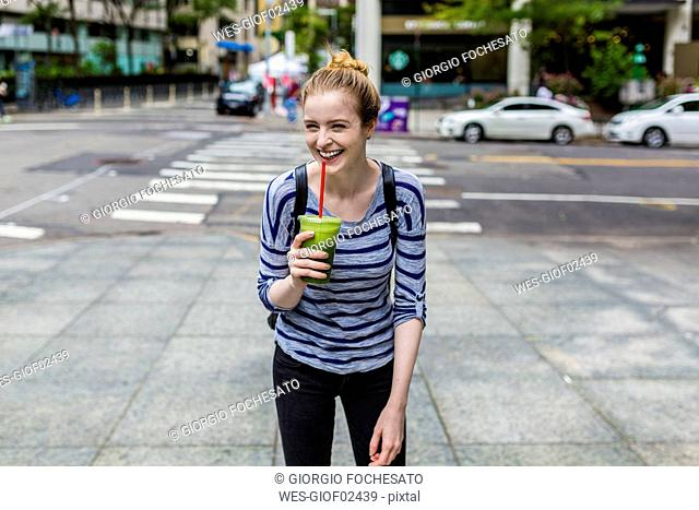 USA, New York City, lauging young woman with a smoothie in Manhattan