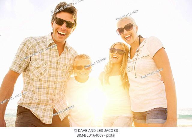 Caucasian family wearing sunglasses on beach