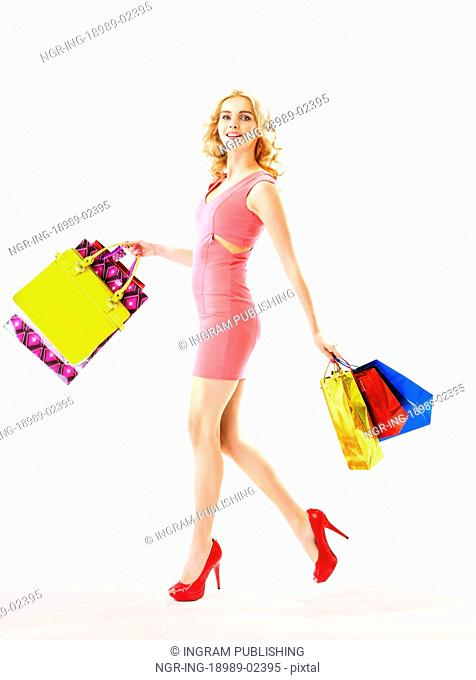 Slim blond woman holding a bunch of colorful bags