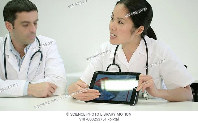 Two doctors in a discussion with digital tablet