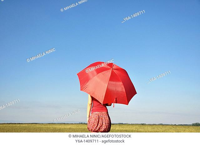 Young woman holding red umbrella