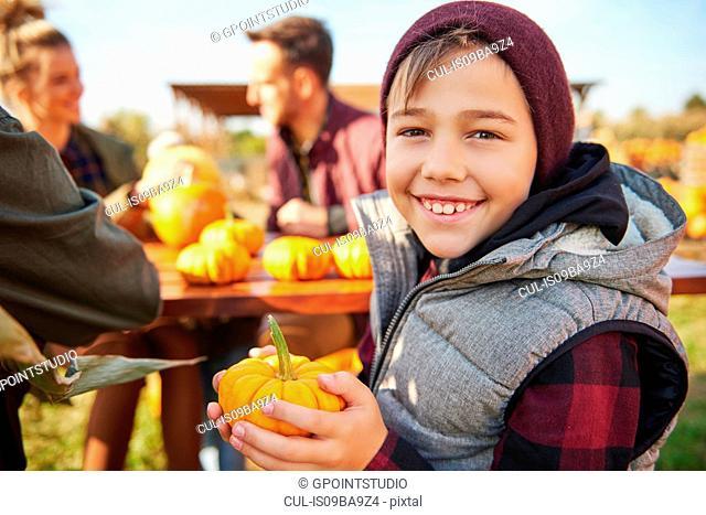 Portrait of boy holding harvested vegetable squash