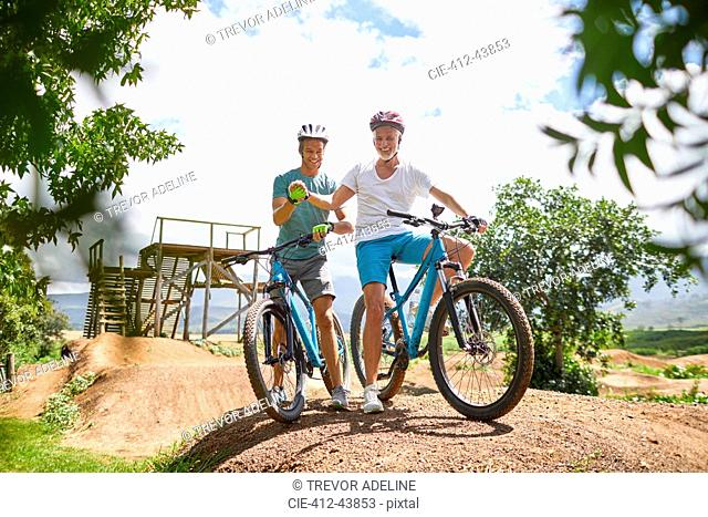 Father and son mountain biking at sunny obstacle course