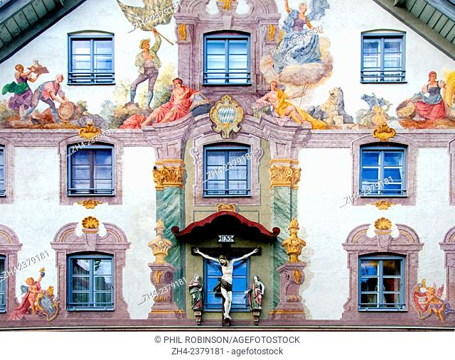 Weilheim, Bavaria, Germany. Painted facade of house on Poltnerstrasse. Statue of Christ on the cross
