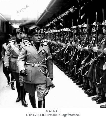 Album Il viaggio del Duce in Germania(Il Duce's tour of Germany): Benito Mussolini, Galeazzo Ciano and Achille Starace pass in teview of soldiers lined up along...