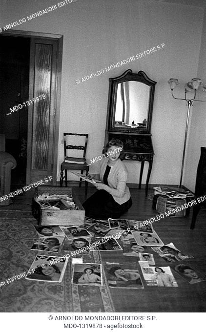 Sylvia Koscina with some magazines. Croatian-born Italian actress Sylvia Koscina (Sylva Koskinon) looking at some magazines piled up on the floor
