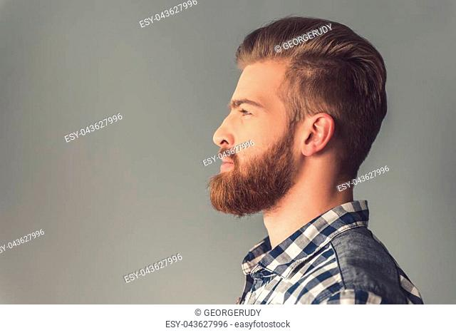 Side view of handsome bearded man in casual clothes, on gray background