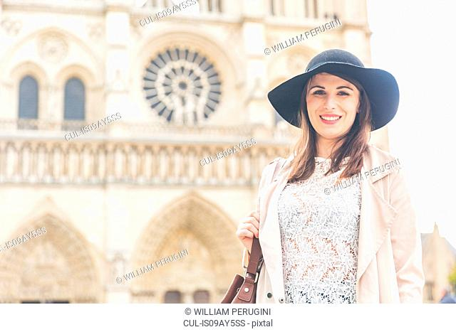 Portrait of stylish young woman in front of Notre Dame, Paris, France